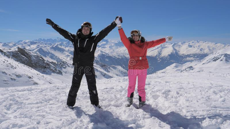 Happy skiers couple stands on the mountain peak and rises their hands stock photo