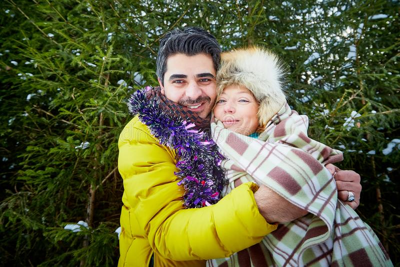 Happy loving couple in snowy winter forest. Ordinary Russian girl and handsome turkish man having fun and hug stock photo
