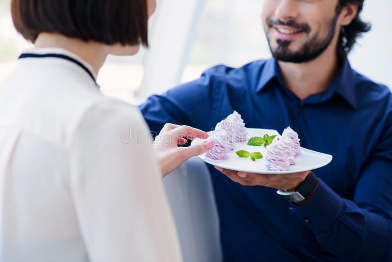 Happy loving couple spending time together. Joyful men is proposing romantic cakes to his girlfriend. He is holding plate and smiling. Woman is sitting and stock image