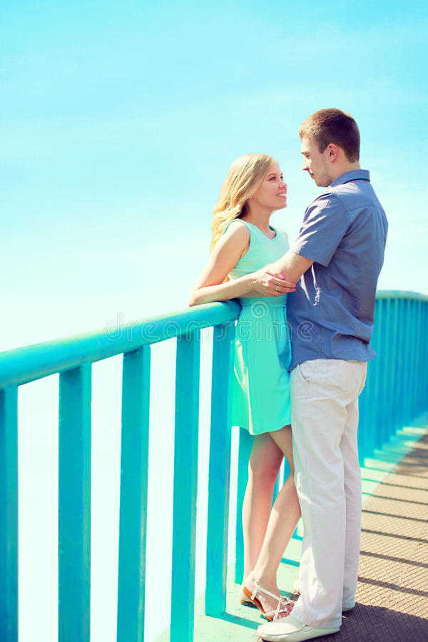 Happy loving couple stands on the bridge. Over a blue sky at city park. Valentines day, relationships concept stock photo