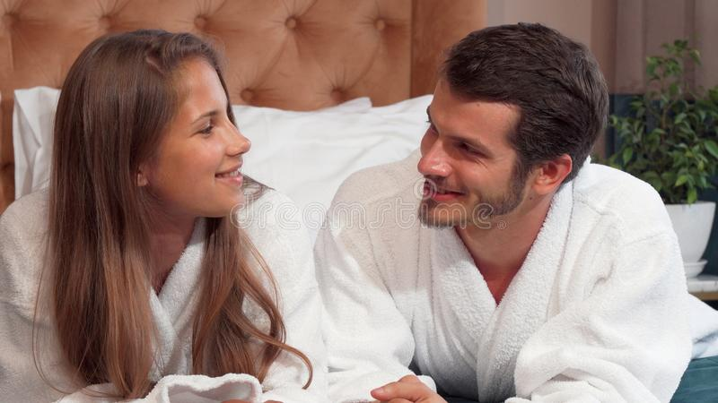 Happy loving couple talking lying in bed together wearing bathrobes royalty free stock photos