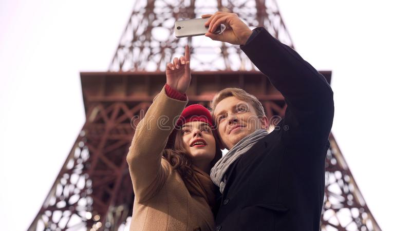 Happy loving couple of tourists doing selfie on background of Eiffel Tower royalty free stock images