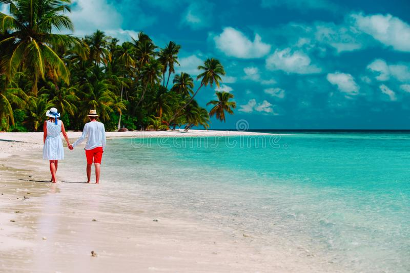 Happy loving couple walk on beach, vacation concept royalty free stock photography