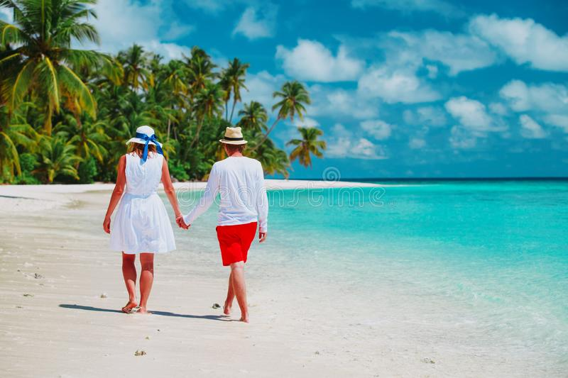 Happy loving couple walk on beach, vacation concept stock images