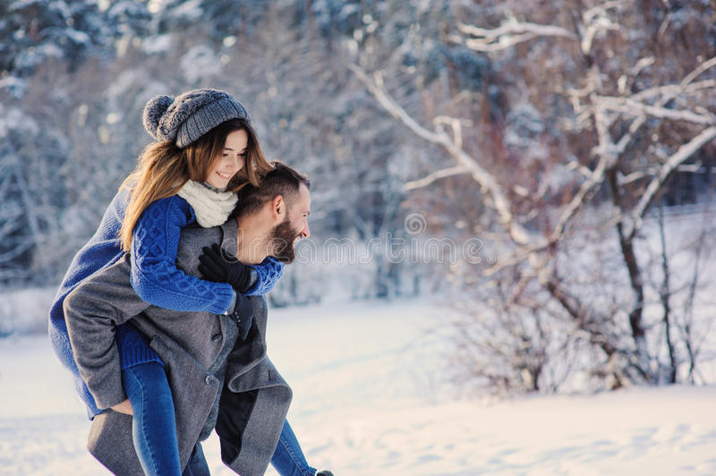 Happy loving couple walking in snowy winter forest, spending christmas vacation together. Outdoor seasonal activities. Lifestyle capture royalty free stock photography