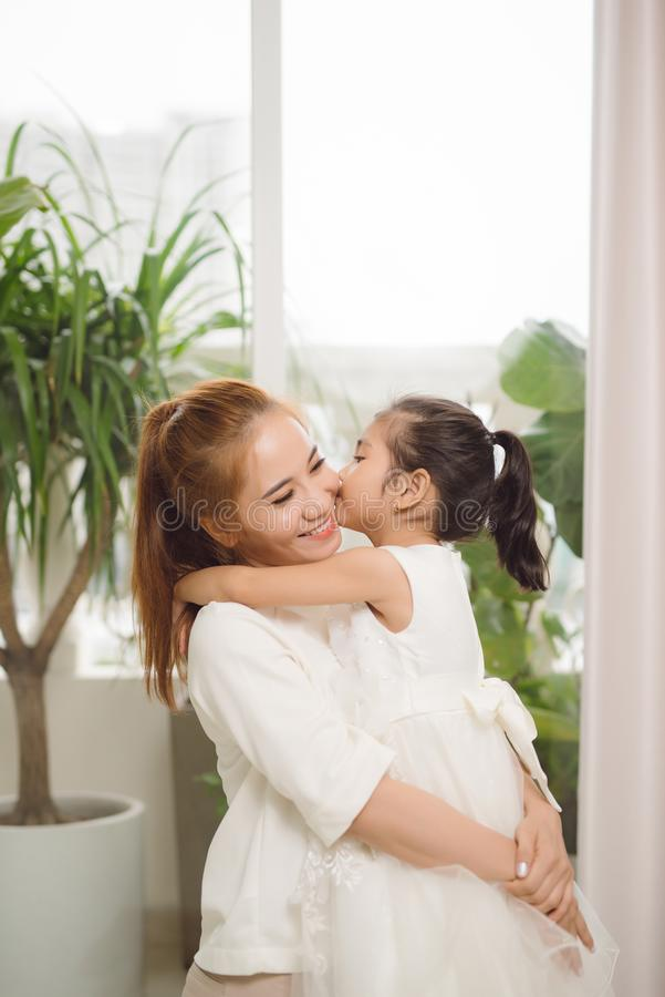 Happy loving family.Asian mother and child girl playing, kissing and hugging stock images