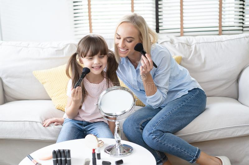 Happy loving family. Beautiful mom with her little cute daughter are doing your makeup and having fun. Mom and daughter holding stock photos