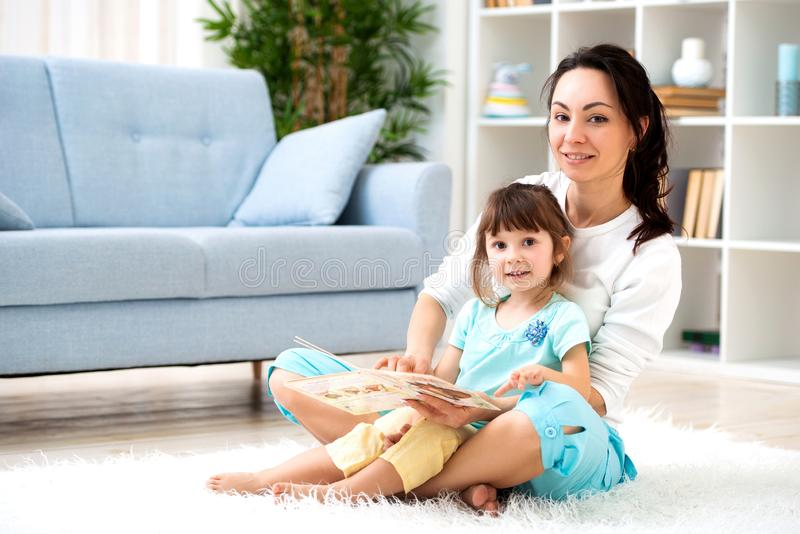 Happy loving family. Beautiful mother and little daughter have fun, play in the room on the floor, hug, smile and fool around stock photography