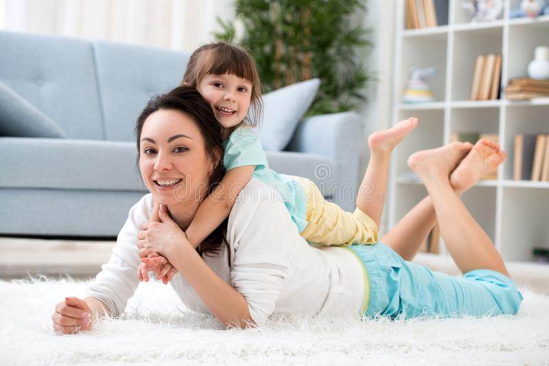 Happy loving family. Beautiful mother and little daughter have fun, play in the room on the floor, hug, smile and fool around stock image