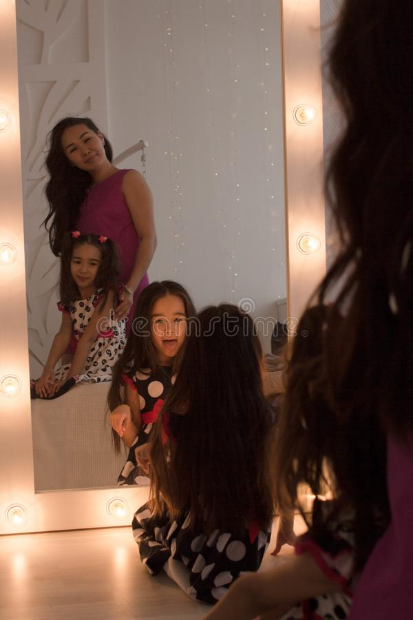 Happy loving family. Cute little girls and mom are sitting near the mirror in the room in the evening dim light.  stock photo