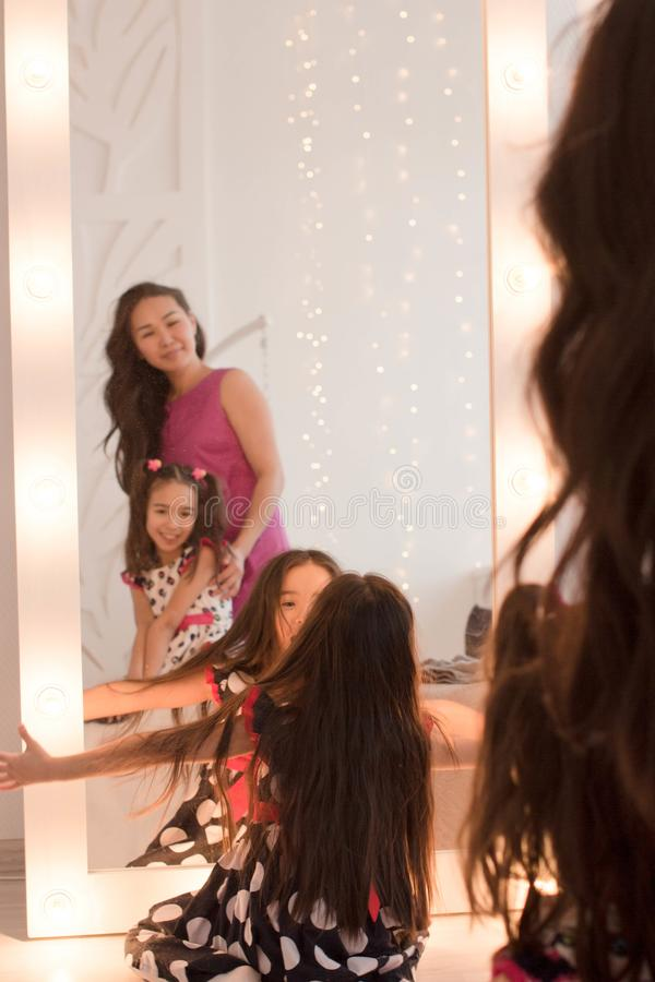 Happy loving family. Cute little girls and mom are sitting near the mirror in the room in the evening dim light.  stock image