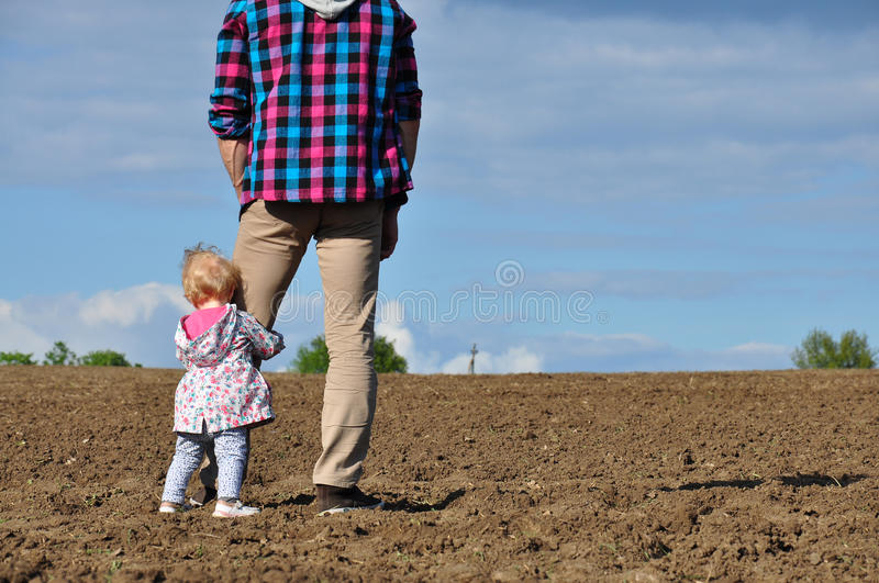 Happy loving family. Father and his daughter child girl playing and hugging outdoors in the field. Cute little girl hugs daddy. stock image