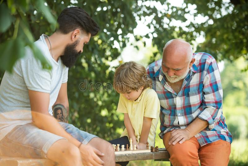 Happy loving family. Grandfather and grandson are playing chess and smiling while spending time together in park royalty free stock photo