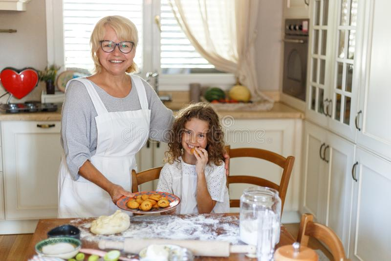 Happy loving family grandmother and her niece are preparing bakery together, having fun in the kitchen. royalty free stock photos