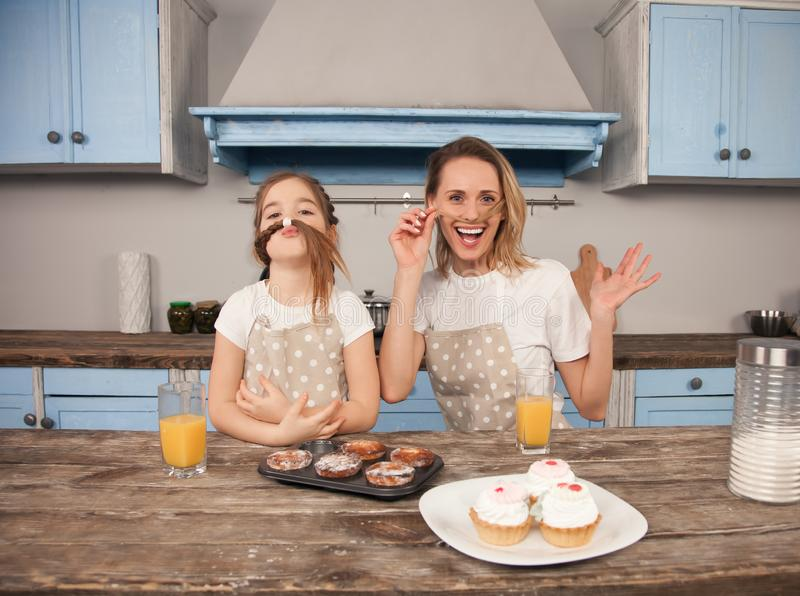Happy loving family in the kitchen. Mother and child daughter girl are eating cookies they have made and having fun in royalty free stock image