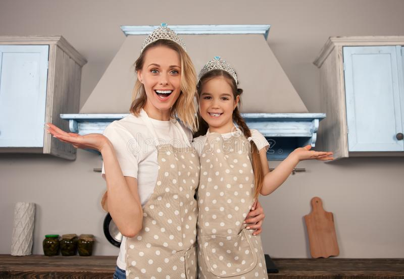 Happy loving family in the kitchen. Mother and child daughter girl are having fun wearing crowns royalty free stock photography