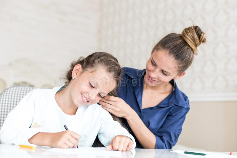 Happy loving family. Mother and daughter are doing hair. dreamy kid girl drawing and paint with color pencils stock images