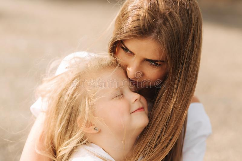 Happy loving family. Mother and her daughter child girl playing and hugging. alley of big trees. close up view royalty free stock image
