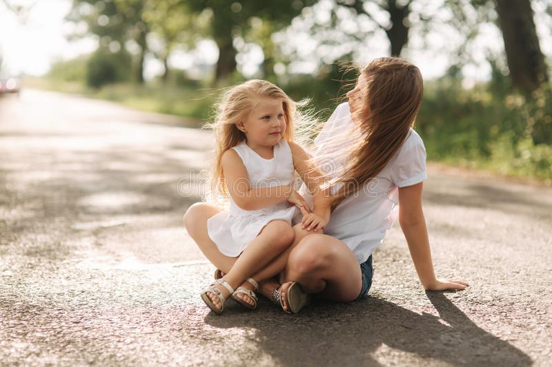 Happy loving family. Mother and her daughter child girl playing and hugging. alley of big trees. close up view stock images