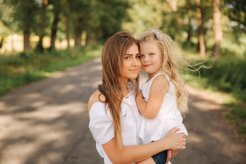 Happy loving family. Mother and her daughter child girl playing and hugging. alley of big trees stock photos