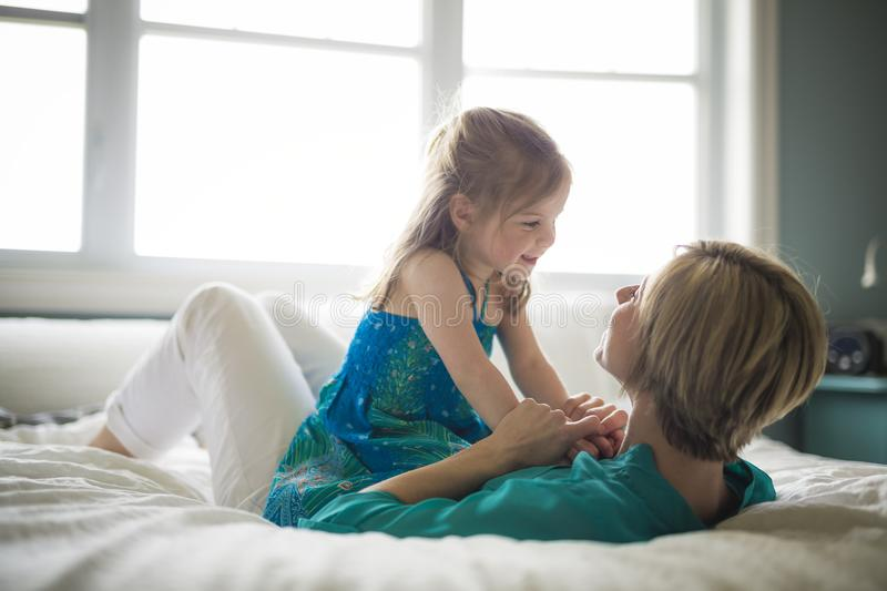 Happy loving family. Mother and her daughter child girl playing and hugging.on bed royalty free stock images