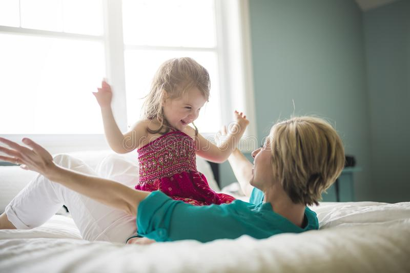 Happy loving family. Mother and her daughter child girl playing and hugging.on bed royalty free stock photo