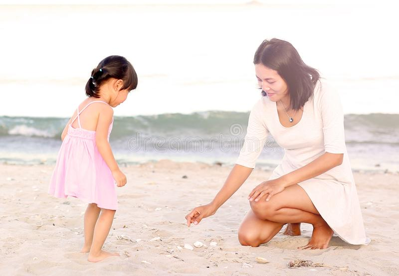 Happy loving family. Mother and her daughter child girl playing sand at the beach royalty free stock photography