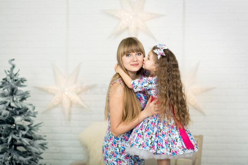 Happy loving family. Mother and her daughter child girl in the same dresses playing and hugging stock photography
