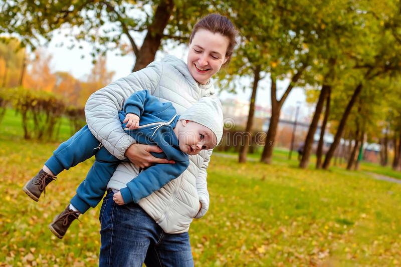 Happy loving family in the park. Mother in white and baby boy in blue having fun, playing and laughing in nature stock image