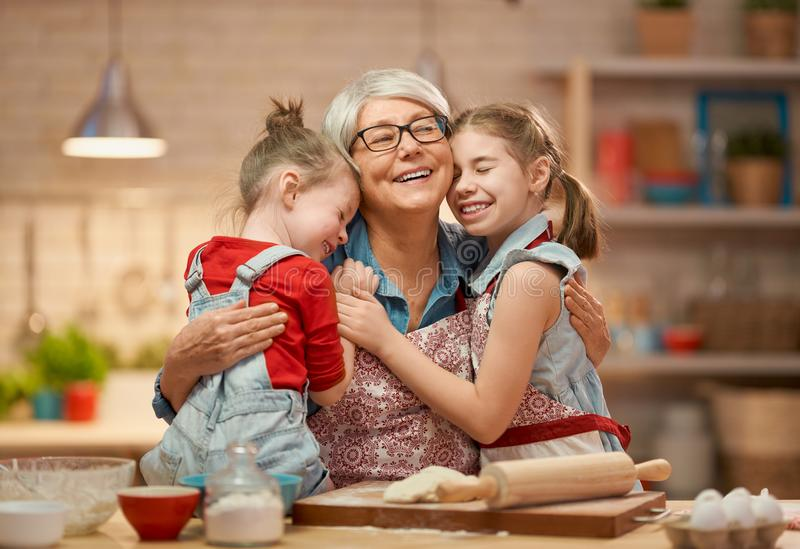 Homemade food and little helper. Happy loving family are preparing bakery together. Granny and children are cooking cookies and having fun in the kitchen royalty free stock photography