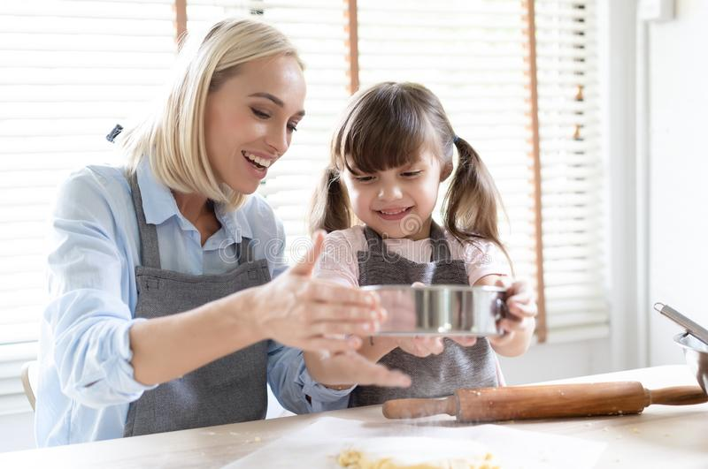 Happy loving family are preparing bakery together. Mom and little cute daughter prepare dough for baking are cooking cookies and royalty free stock photos