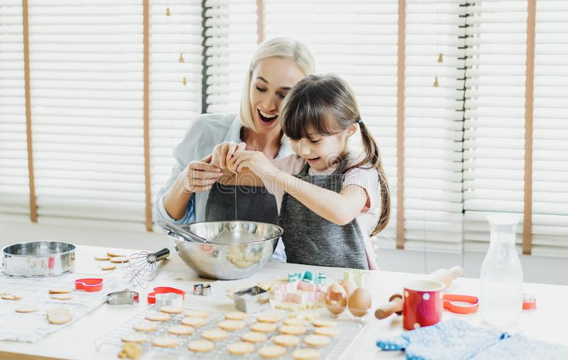 Happy loving family are preparing bakery together. Mother and her daughter child girl are cracking an egg into a bowl, bake stock photo