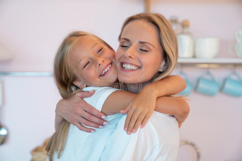 Happy loving family. Pretty mother and her cute young daughter are hugging and cuddling smiling stock photo