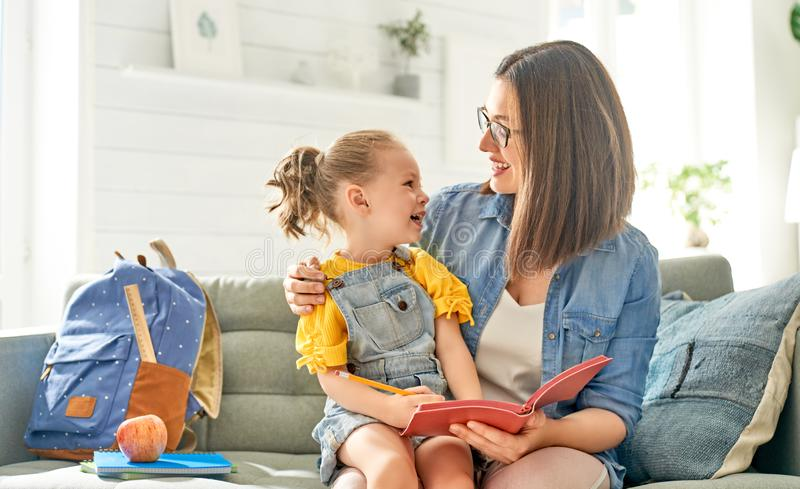 Mother and her daughter are writing in notebook stock photography