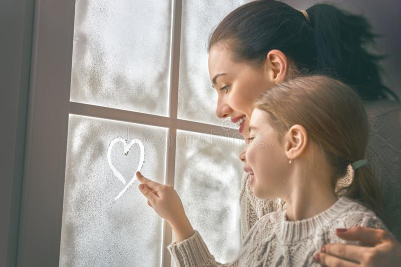 Family drawing a heart on frozen glass stock image