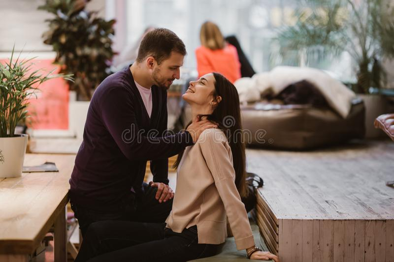Happy loving guy puts his hands at the girl`s shoulders sitting at the table in the cafe and looks at her royalty free stock photos