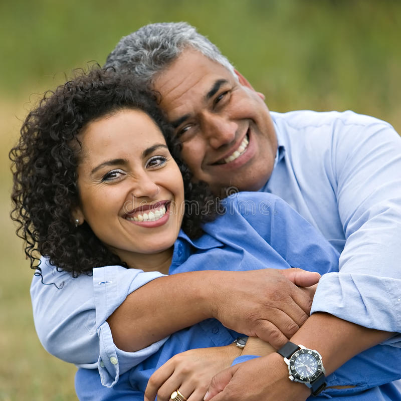 Happy Loving Hispanic Couple. Attractive fun smiling hispanic couple cuddling in outdoor natural light square format