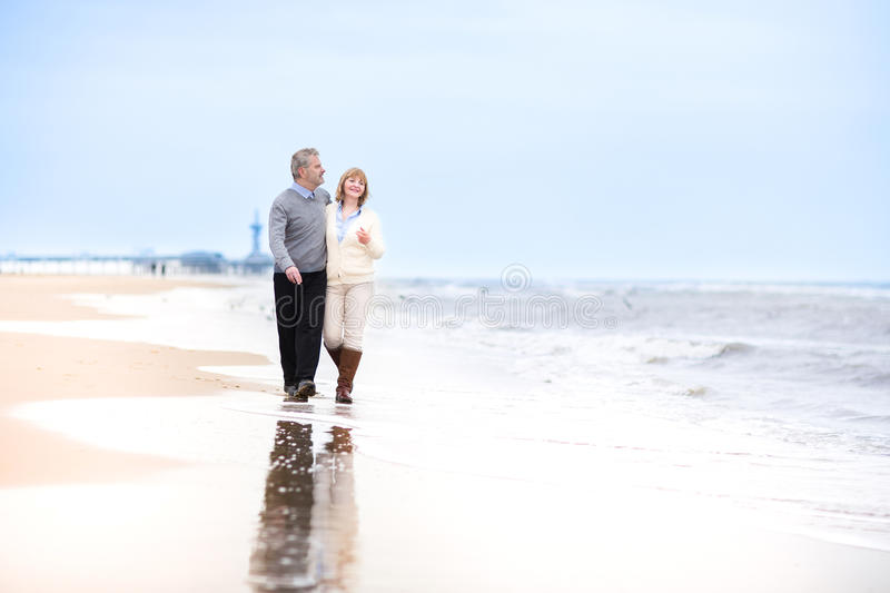 Happy loving middle aged couple walking on beach. Happy loving middle aged couple walking on a beautiful beach in Holland royalty free stock image