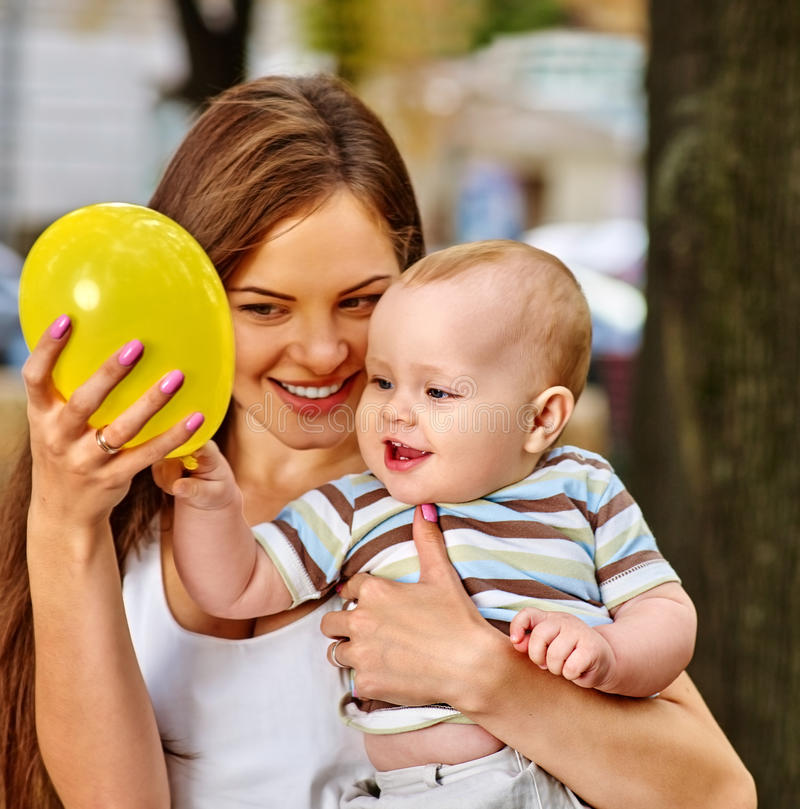 Happy loving mother and her baby outdoors. Happy mother and her baby play with balloon outdoors in park. Baby keeps balloon. First baby birthday royalty free stock photo
