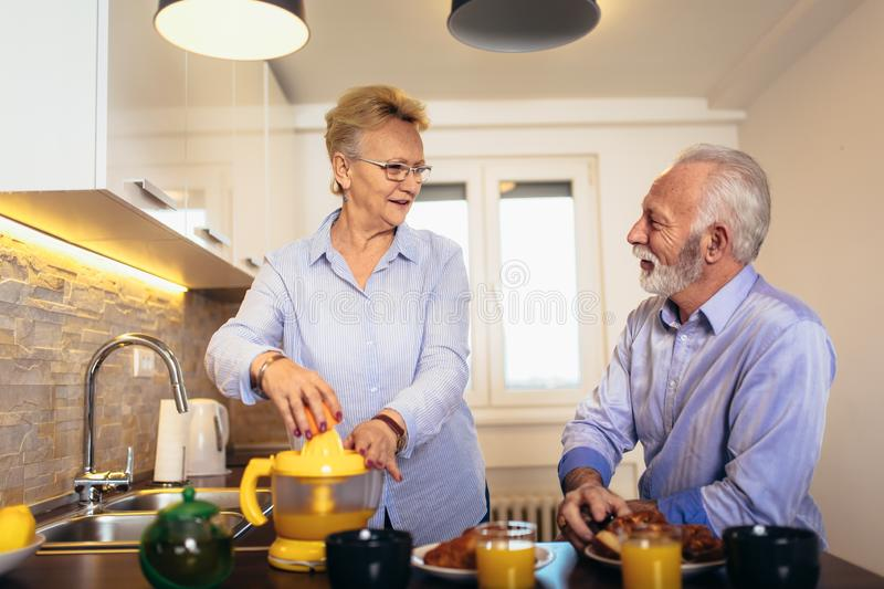 Senior couple having fun preparing healthy food on breakfast in the kitchen royalty free stock photos