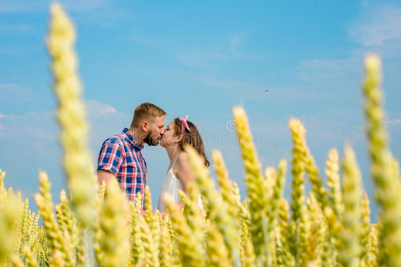 Happy loving young adult couple spending time on the field on sunny day. stock photo