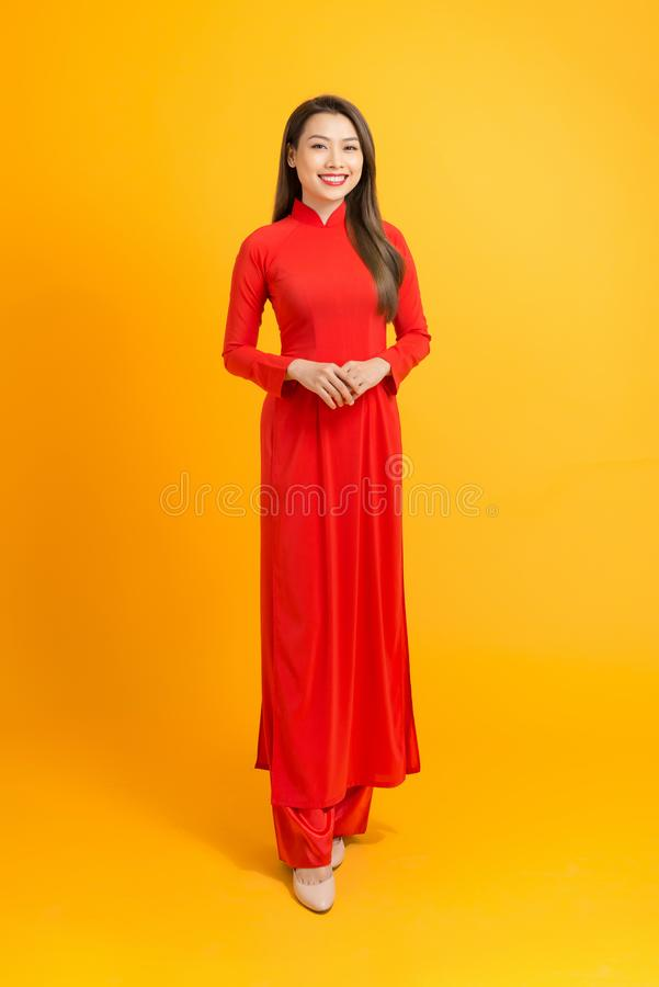 Happy lunar new year. Asian girl in vietnamese traditional dress ao dai on yellow background.  royalty free stock image