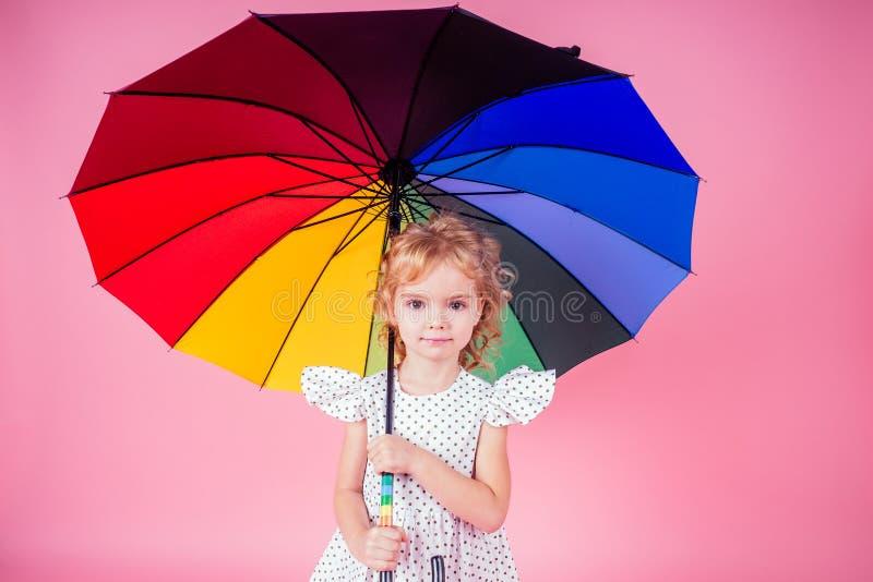 Happy lustige schöne Blondine mit blauen Augen Kind mit Regenbogen bunten Schirm in rosa Hintergrund im Studio Girl-Kind stockfotos
