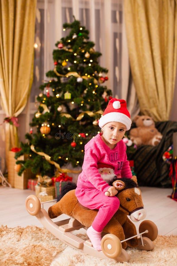 Happy Mädchen, das zu Hause auf einem Pferd vor dem Weihnachtsbaum reitet stockfotografie