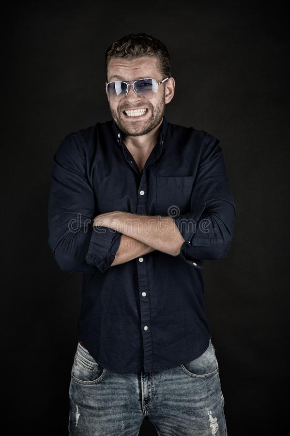 Happy macho in glasses, shirt, jeans with folded hands, fashion. Man with smile on bearded face on dark background. Fashion, style, accessory. Beauty, barber stock photo
