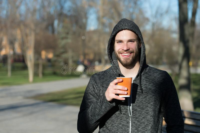 Happy macho in hood hold disposable coffee cup in sunny park. Bearded man smile with takeaway drink on fresh air. Coffee or tea mo. Od. Drink and food outdoor royalty free stock photos
