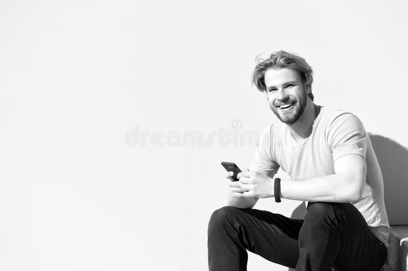 Happy macho with smartphone on sunny outdoor. Bearded man smile with mobile phone on grey wall. Guy with beard and blond. Hair in casual tshirt. New technology stock images