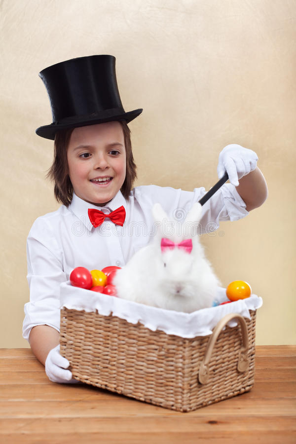 Happy magician boy conjuring an easter rabbit and colorful eggs stock photo