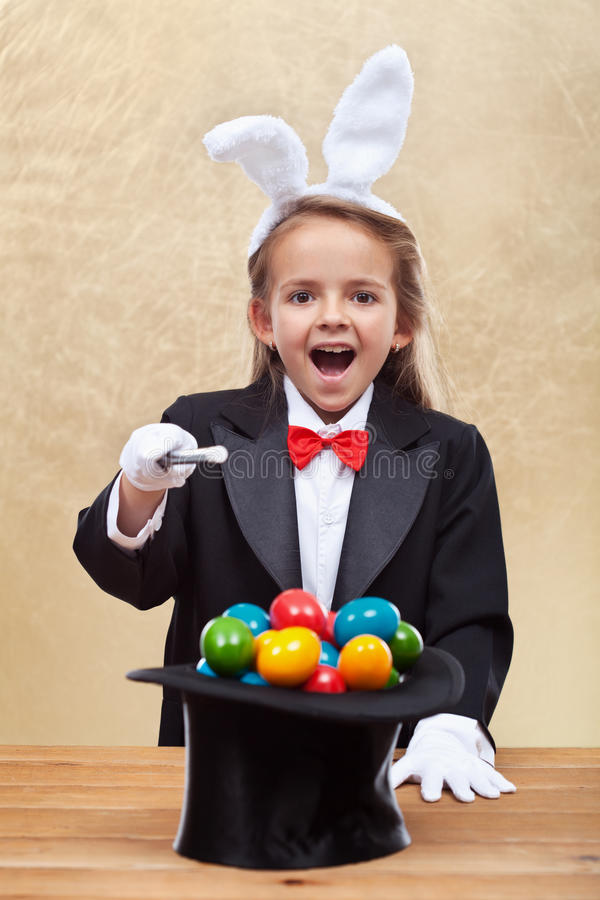 Happy magician girl conjuring colorful easter eggs royalty free stock images