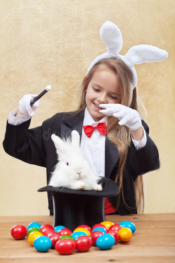 Happy magician girl conjuring up the easter bunny and eggs stock photography